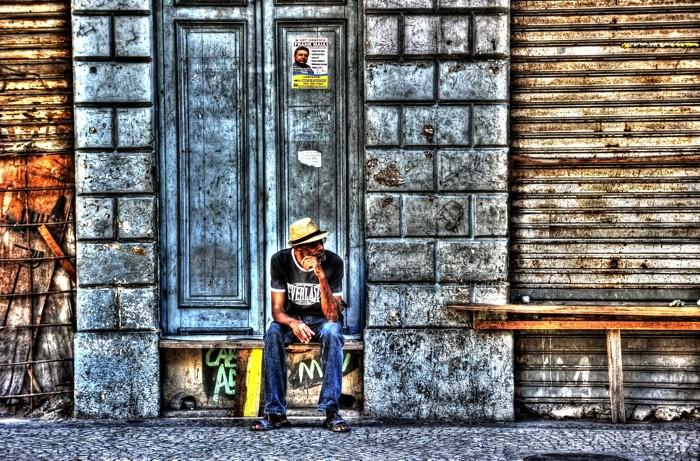 Hady Khandani, HDR - MAN IN FRONT OF A DOOR 2 (HADYPHOTO, Mann, Menschen, Tür, Hauswand, sitzen, warten, chillen,  Fotografie, Wunschgröße, Wohnzimmer, Treppenhaus, bunt)