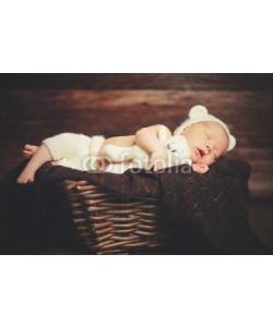 JenkoAtaman, Cute newborn baby in bear hat sleeps in basket with toy teddy be