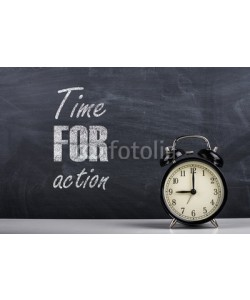 dmshpak, Retro alarm clock and the text time for action written with chalk on the blackboard.