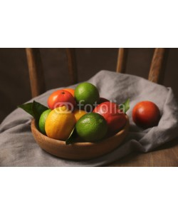 Africa Studio, Composition of different citrus fruits in bowl on wooden chair