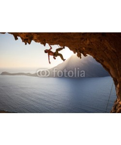 Andrey Bandurenko, Rock climber climbing along roof in cave at sunset
