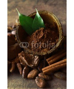 Africa Studio, Bowl with aromatic cocoa powder and green leaf on wooden background, close up