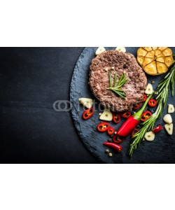 Alex Green, Fried fresh large beef burger with herbs and garlic on black slate, top view, space for text